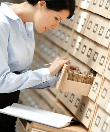 Mujer bonita busca algo en el catálogo de fichas compuesto de un conjunto de cajas de madera en la biblioteca. Educación