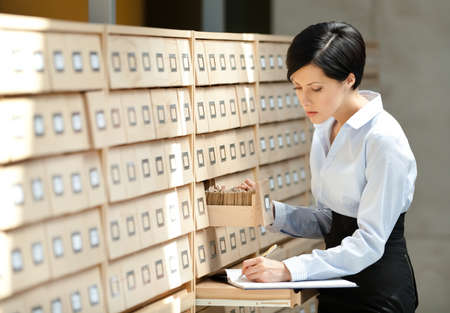 pencil skirt: Pretty woman searches something in card catalog composed of set of wood boxes at the library. Study