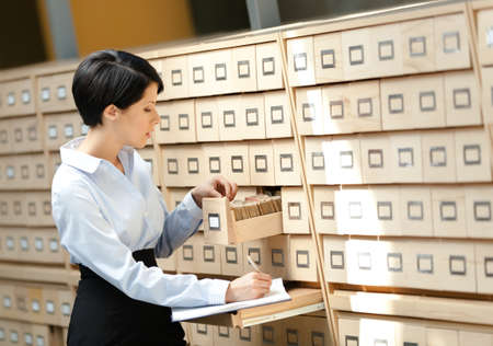 suit skirt: Woman searches something in card catalog composed of set of wood boxes at the library. Education