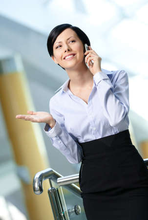 skirt suit: Business woman in business suit talks on mobile. Leadership