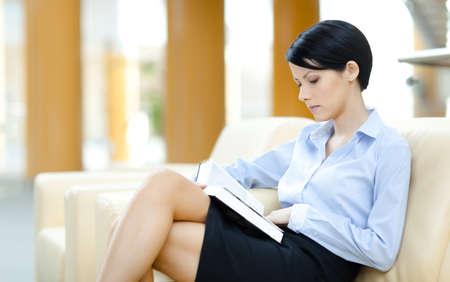 falda corta: Mujer de negocios se basa en el libro de sofá en la sala de lectura Foto de archivo