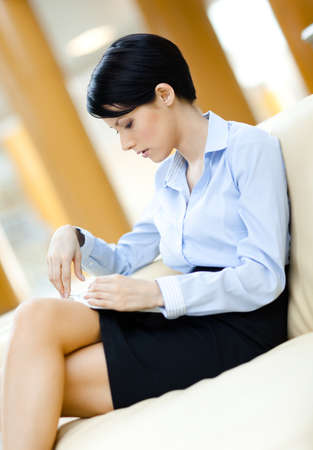 insight: Busy business woman rests at the sofa reading book at the hall Stock Photo
