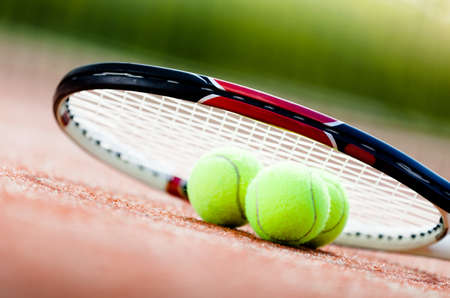 avocation: Tennis racket with balls on clay tennis court Stock Photo