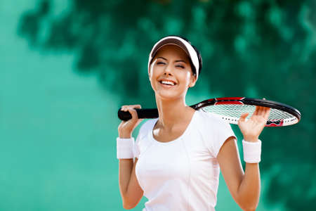 Successful sportswoman with racket at the tennis court. Healthy lifestyle photo