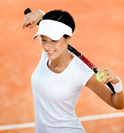 Woman in sports wear keeps tennis racket and ball on her shoulders at the clay tennis court. Match photo