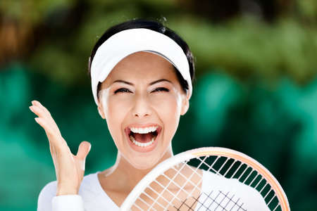 Close up of happy woman with tennis racket at the tennis court. Prize photo