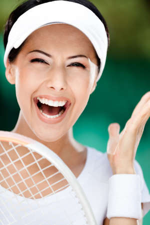 Close up of happy woman with tennis racket at the tennis court. Award photo