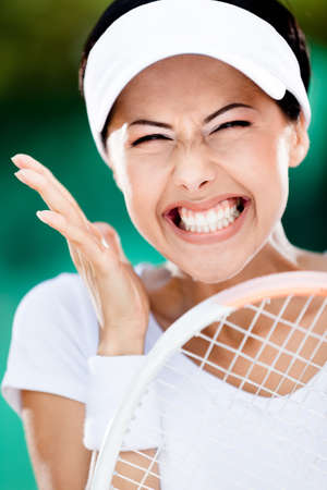 Close up of happy woman with tennis racket at the tennis court. Trophy photo