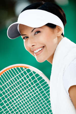 Close up of successful tennis player with towel on her shoulders photo