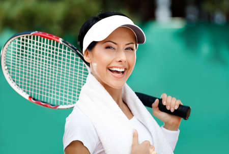 Female tennis player with towel on her shoulders. Active pastime photo