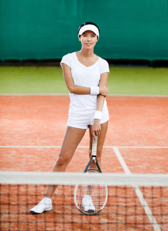 Woman in sportswear with tennis racquet at the tennis court photo