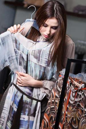 tries: Pretty girl tries a dress on Stock Photo