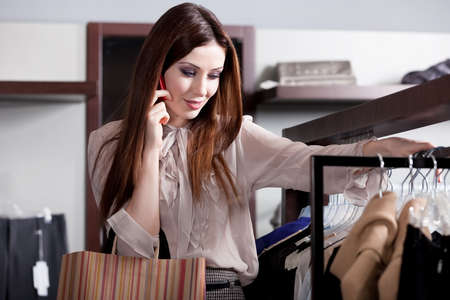 Speaking on the phone and choosing clothes in the store Stock Photo - 15434055