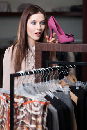 Woman admires excellent fuchsia shoes in the shopping mall photo