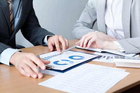 Two business people discuss meeting targets sitting at the business table with documents Stock Photo - 15541632
