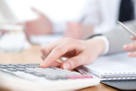Business people counting on calculator sitting at the table. Close up of hands and stationery photo