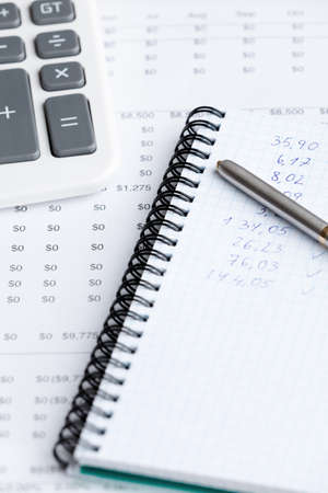Close up of business stationery: writing pad, pen, calculator and some documents photo
