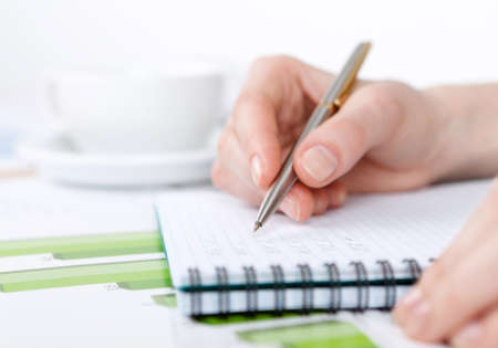 heap up: Close up of hand making notes in the writing pad lying on the diagrams Stock Photo