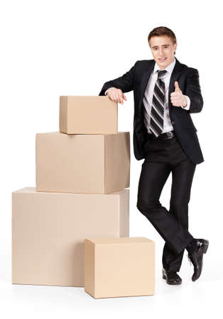 Manager in suit stands near pile of containers, isolated on white photo