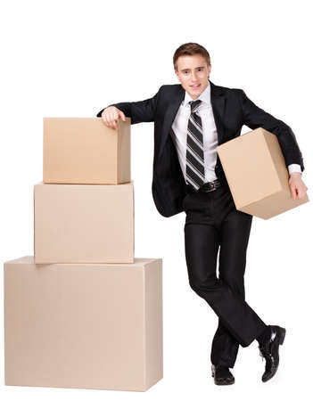 Manager in suit stands near pile of cardboard boxes, isolated on white photo