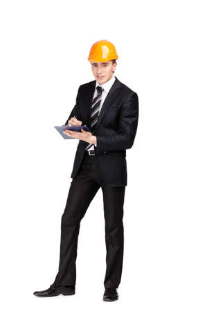 Making notes man in orange hard hat and suit, isolated on white photo