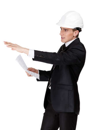 Businessman in white helmet pointing at something hands blueprint, isolated on white Stock Photo - 15530465