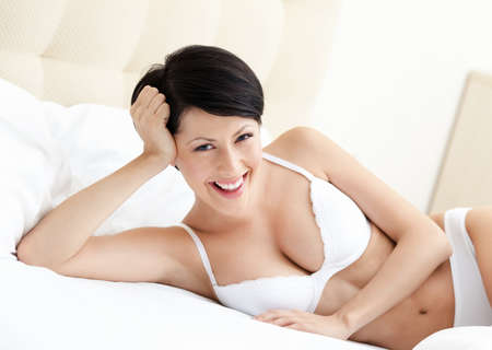 Woman in white bra is lying in the comfortable bed with white bedclothes photo