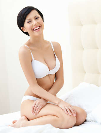 brassiere: Half nude woman sits on the bedstead