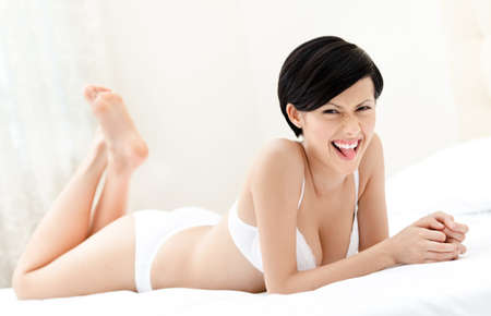 figure out: Woman in underwear is lying in the bed with white bedclothes, white background