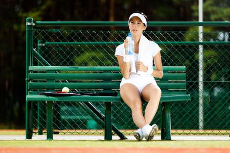 �sportswear: Jugador de tenis femenino descansa con una botella de agua en el banquillo en la pista de tenis