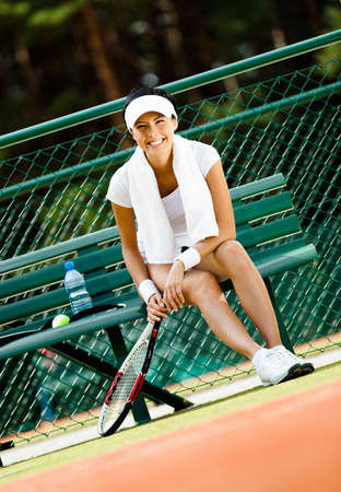 Young female tennis player rests with bottle of water on the bench at the tennis court photo