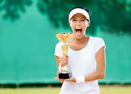 Tennis player won the cup at the sport competition. Award photo
