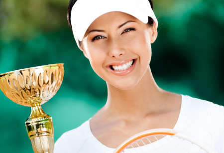 Professional tennis player won the cup at the sport competition. Victory photo
