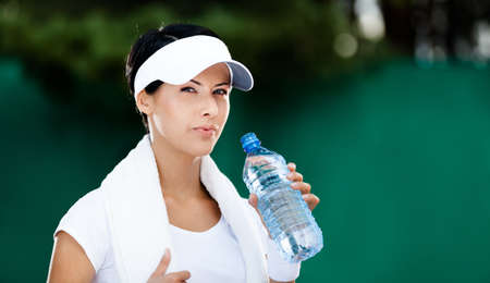 Sporty woman with bottle of water after tennis competition photo