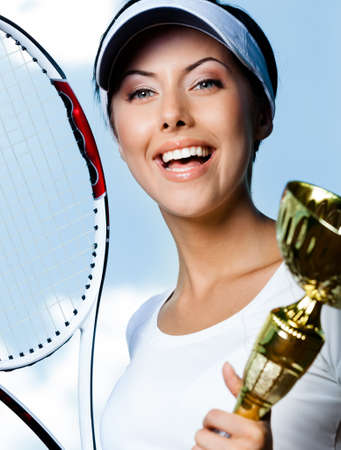 Close up of female tennis player with tennis racket and cup against the sky Stock Photo - 15574654