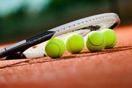 raqueta tenis: Cierre de vista de raqueta de tenis y pelotas en la cancha de tenis de arcilla Foto de archivo