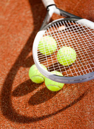 avocation: Close up of tennis racket and balls on the clay tennis court Stock Photo