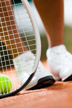 Legs of sportswoman near the tennis racket and balls Stock Photo - 15541669