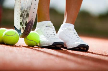 tenis: Las piernas de atleta cerca de la raqueta de tenis y pelotas