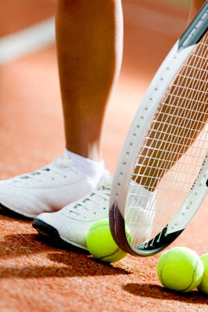 Legs of sportive girl near the tennis racket and balls photo