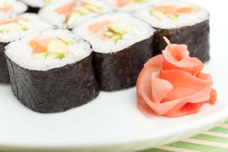 Sushi rolls on the white plate which is on green mat photo