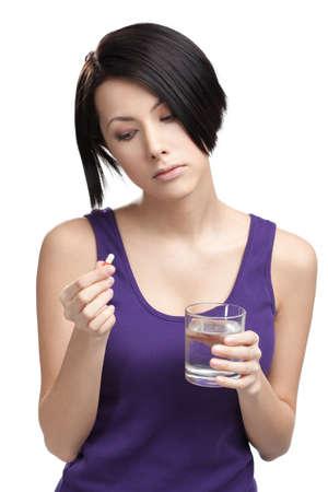inmunidad: Mujer con un vaso de agua toma píldoras, aislado en blanco. Tomar medicamentos