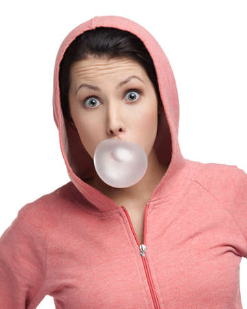 blow out: Female in sweatshirt blows out pink bubble gum, isolated on white