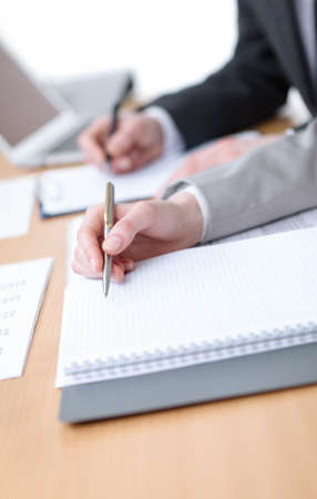 Business people making notes in notebooks sitting at the table  Close up of hands photo