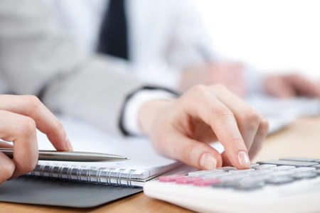 calculating: Business people counting on calculator sitting at the table  Close up view of hands and stationery