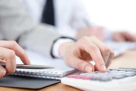 calculadora: La gente de negocios contando con calculadora sentado en la mesa de Cierre de vista de las manos y papeler�a