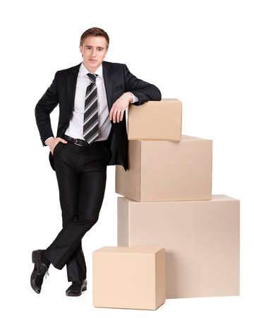 packaging move: Manager in suit stands near pile of pasteboard boxes, isolated on white Stock Photo
