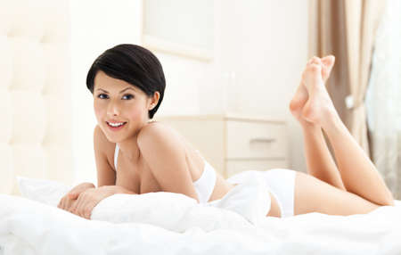 Woman in underwear is lying in the bedstead photo