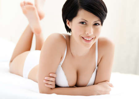 Woman in underwear is lying in the bed with white bed linen, white background photo