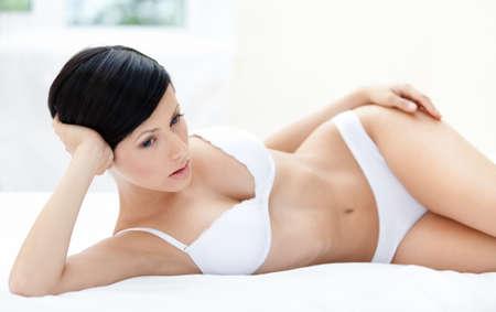 ropa interior: Mujer en ropa interior yace en la cama suave, fondo blanco